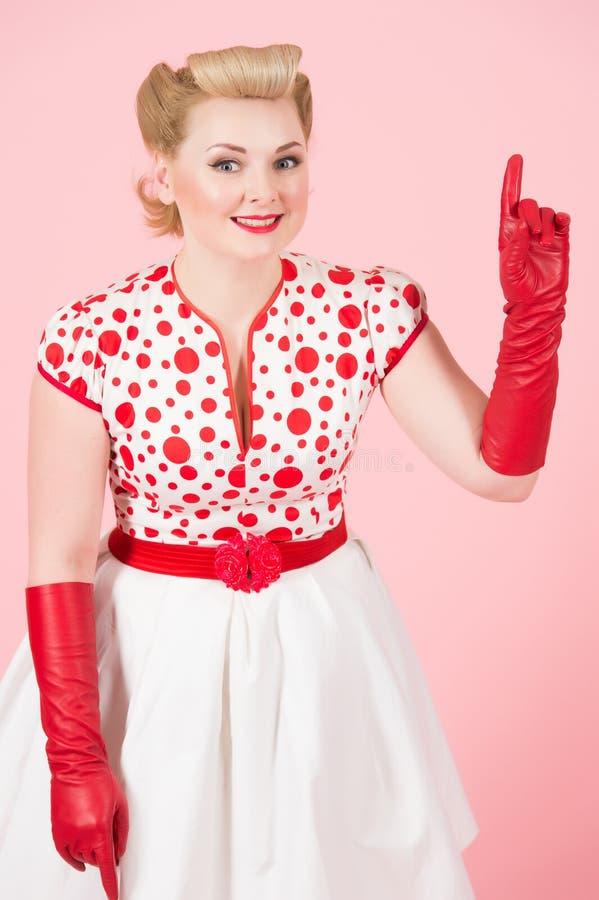 Fenale blond avec la boucle blonde se dirigeant par le doigt La fille Pin- révèle l'espace de copie à la main Madame recommandent photographie stock libre de droits