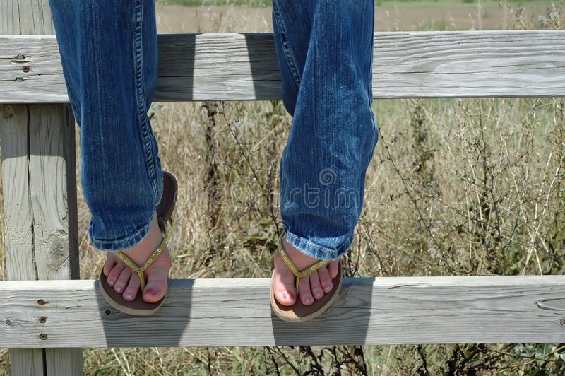 On the Fence. Partial shot of girl sitting on fence wearing jeans and yellow flip-flops stock images