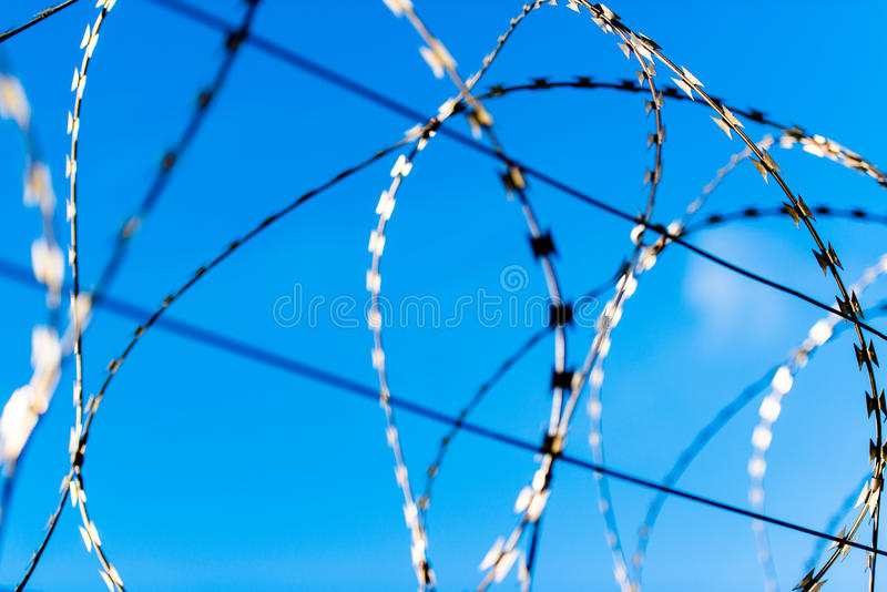 Fence with barbed wire. In front of great blue sky - concept for freedom, liberty or prison royalty free stock photos