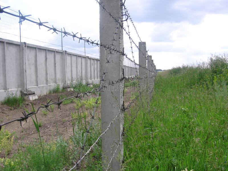 Fence barbed wire fence covers prohibited restricted area industrial strategic facility under protection. The fence is barbed wire on poles is forbidden overlaps royalty free stock photography
