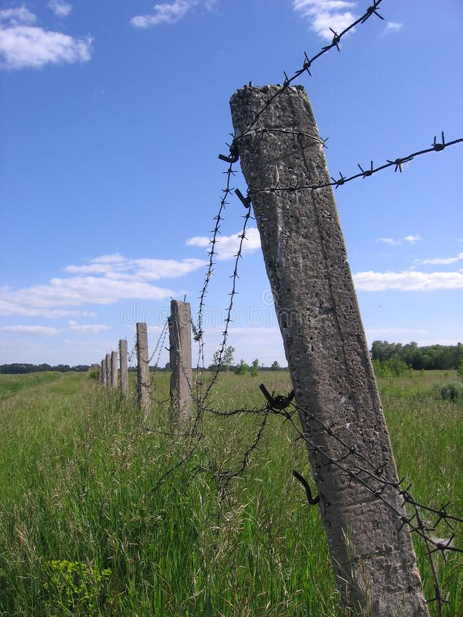 The pasture is fenced Fence barbed wire fence covers prohibited restricted area industrial strategic facility under protection. The fence is barbed wire on poles stock image