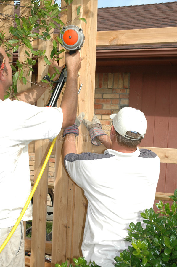 Fence Building. Two men work together to construct a brand new fence that will be board on board stock images
