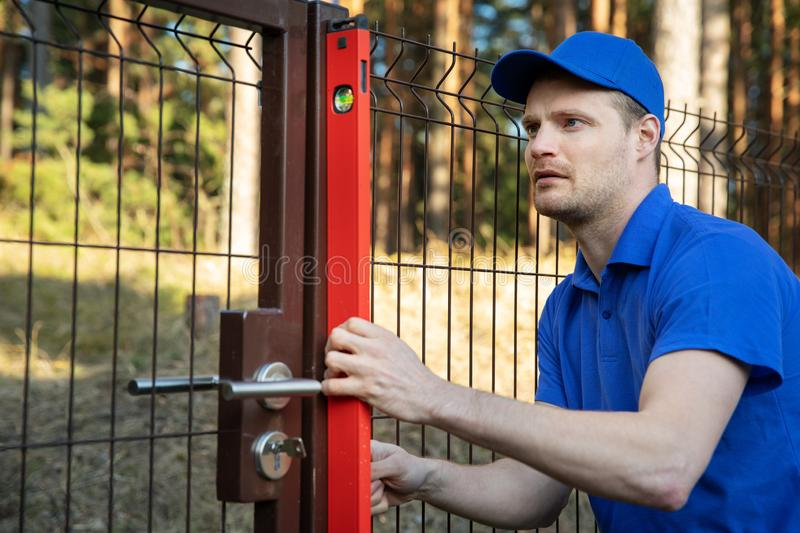 Fence construction - worker check the level of metal post stock photos