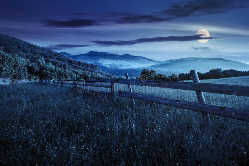 Fence on hillside meadow in mountains at night stock photo