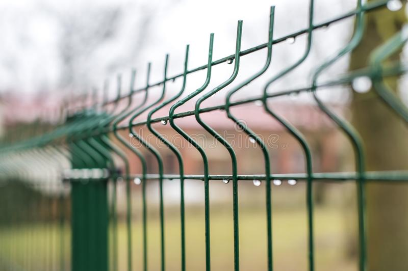 A fence of iron bars green. Filmed against a brick building red brick. On the background of the Park royalty free stock photo