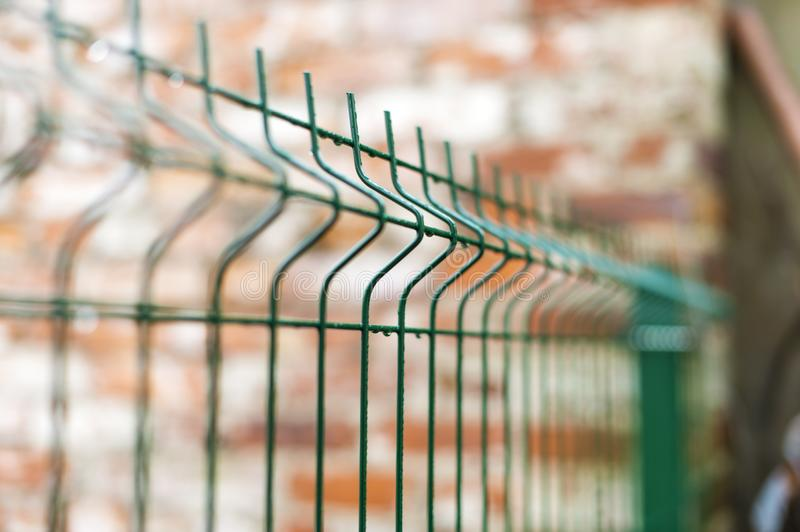 A fence of iron bars green. Filmed against a brick building red brick. On the background of the Park stock photography