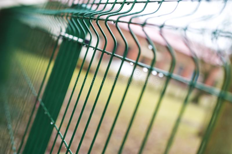 A fence of iron bars green. Filmed against a brick building red brick. On the background of the Park royalty free stock photos