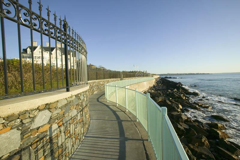 Fence lines the Cliff Walk, Cliffside Mansions of Newport Rhode Island royalty free stock images