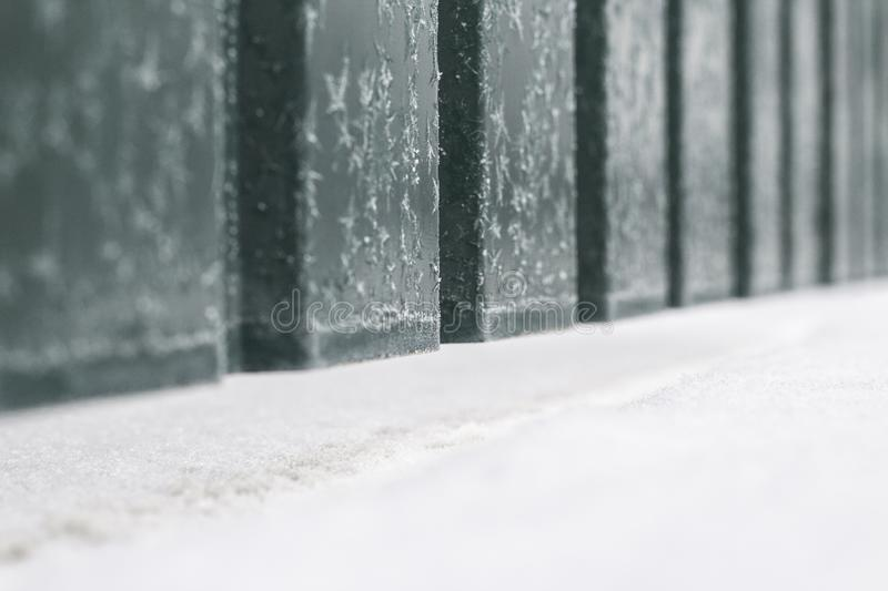 The fence made of metal green color with white snow near it and frozen water on it stock photos