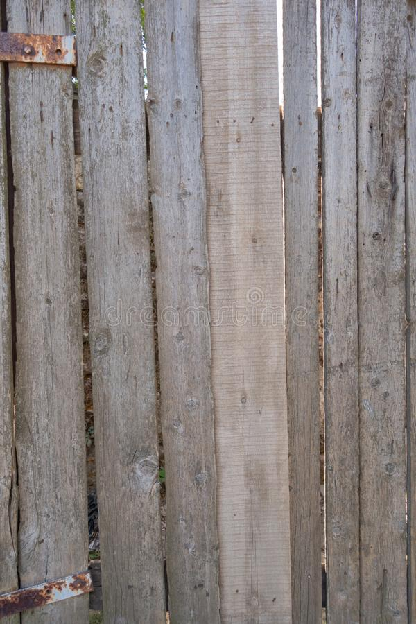 Fence from old weathered pine boards. Texture of natural aged wood. Woodworm holes, rusty nails. Creative vintage background. Close, closeup, metal, wall, dark royalty free stock photos