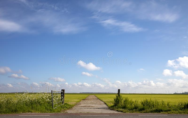 Fence that is open in agricultural land, bright green meadow with high sky with clouds and clear horizon and some turbines in the stock photos