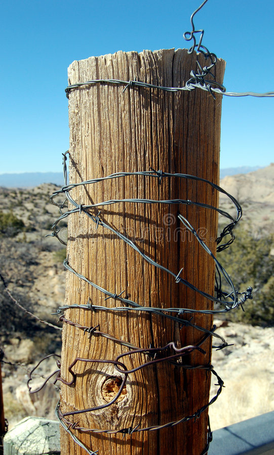 Fence Post. Rugged wooded fence post with barbed wire stock photography