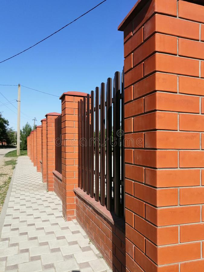 fence of red brick and metal vertical stripes - shtaketin. perspective view against the blue sky. idea - building a private house. stock image