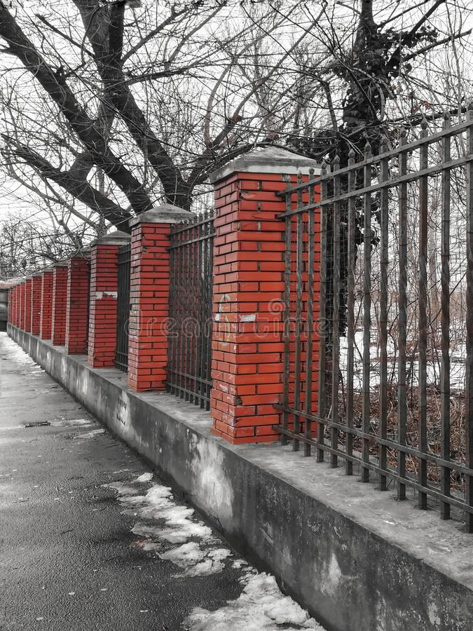 Fence red brick poles, metal and concrete. Fence of red brick poles, metal and concrete on a street  in the city royalty free stock image