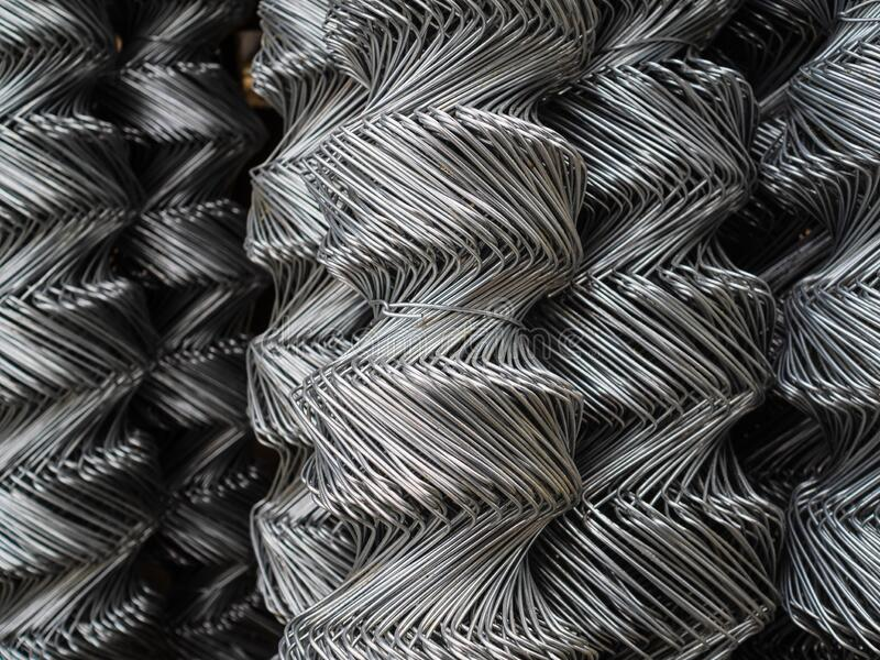 Fence rolls are made of galvanized steel mesh. Large, twisted cells on the fence. Warehouse sales of metal fencing stock image