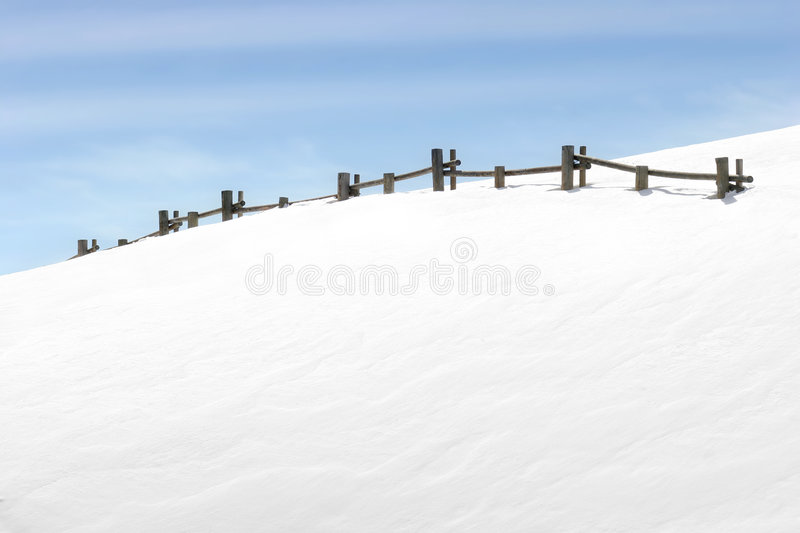 Fence on snowy hill royalty free stock photos