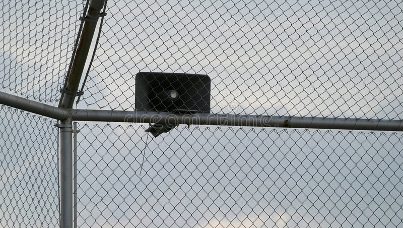 Fence and Speaker. A chain link fence and loudspeaker. May be used for prison scenes, announcements, security, ball parks, military complex or texture for design stock image
