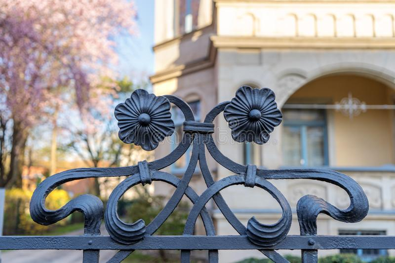 Fence steel art deco flowers winding. Steel fence with ornamental art deco style flowers centered in the picture frame in front of a building being blurred royalty free stock image
