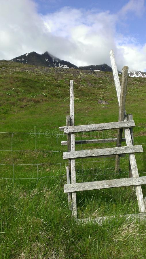 Icelandic hike starts with wooden ladder. A makeshift wooden slat ladder extends over a fence yielding access to a mountain hike through Icelandic meadows royalty free stock photo
