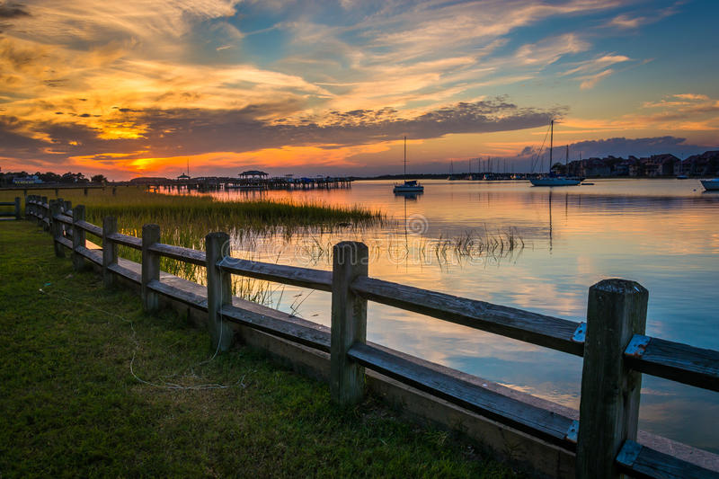 Fence and sunset over the Folly River, in Folly Beach, South Car. Olina royalty free stock image
