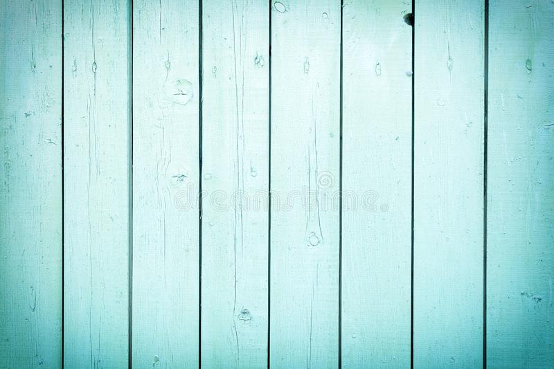 A fence of vertical light turquoise boards. Blank background with a texture of wooden slats. royalty free stock image