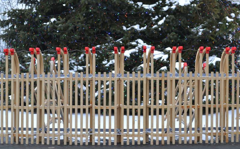 A fence of wooden sledges with a cristmas tree in the background stock photos