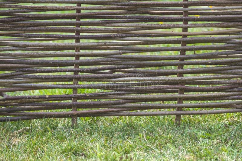 Fence of wooden twigs on green grass. Natural tree trunk texture. Garden decor, barrier, border, boundary. Spring, summer season stock photos