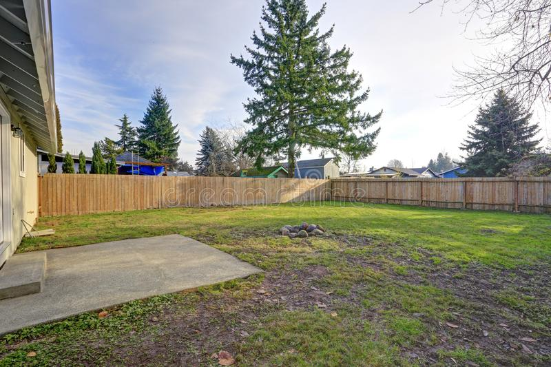 Spacious backyard with wooden fence and fire pit stock photos