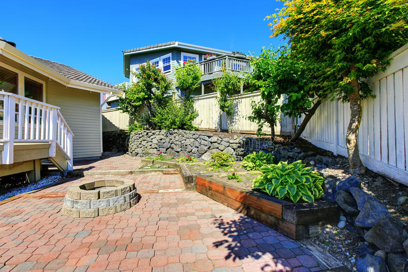 Fenced backyard with rocks desing and concrete tile walkway. royalty free stock photo