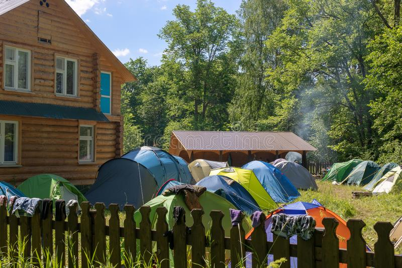 Fenced, guarded camping base with tents. Near the house, gazebo and a place for a fire. stock photography