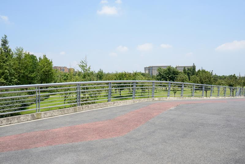 Fenced highway bridge with tarred roadway on urban fringe in su royalty free stock photography