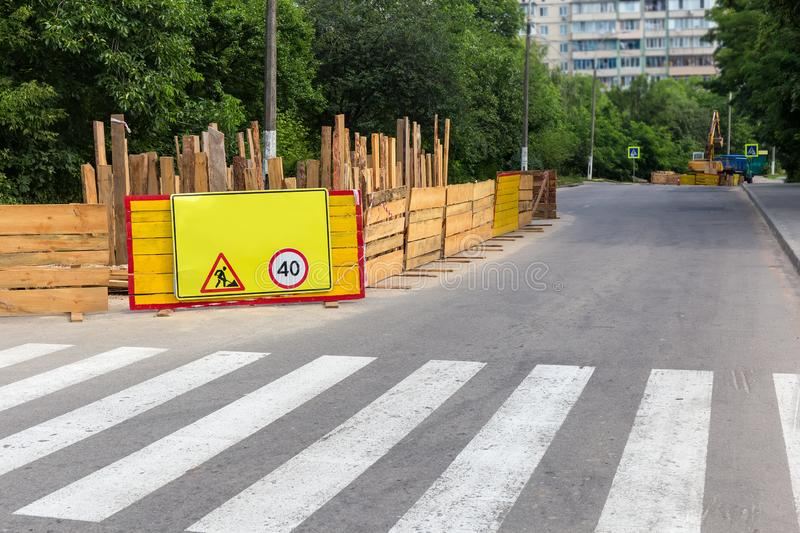Fenced section of city street during of a roadworks. Fragment of city street with fenced section, marked with warning road signs during of a roadworks in summer royalty free stock photo