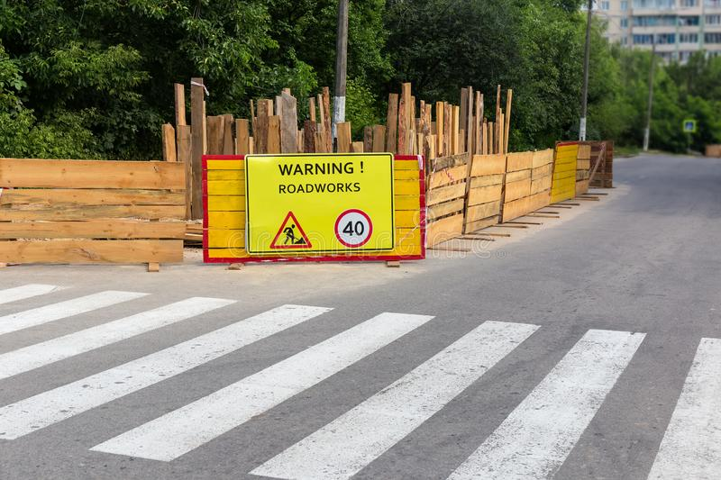 Fenced section of city street during of a roadworks. Fragment of city street with fenced section, marked with warning shield and road signs during of a road royalty free stock photo
