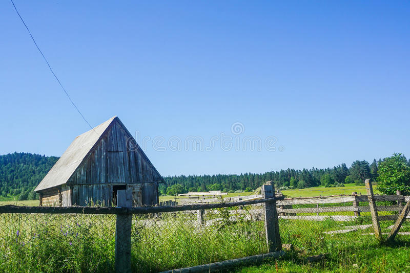 Fenced wooden hut in the meadow royalty free stock images