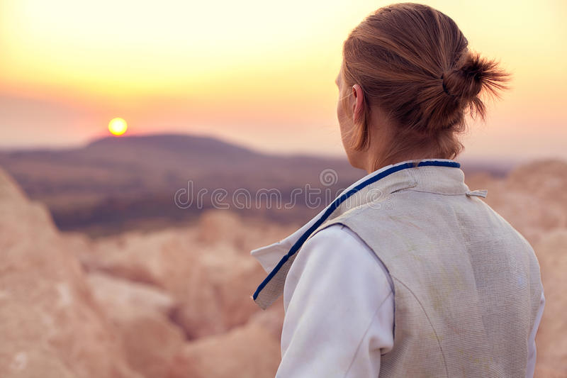 Fencer man on the rocky background and looking forward to the sun goes down. Back view close-up portrait of a fencer man wearing white fencing costume on the stock photo