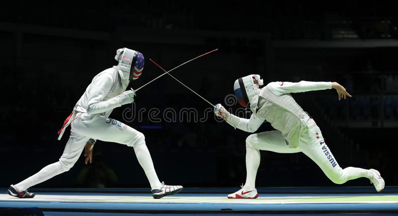 Fencer of Team USA L competes against Team Russia fencer in the Men`s team foil of the Rio 2016 Olympic Games. RIO DE JANEIRO, BRAZIL - AUGUST 12, 2016: Fencer stock images
