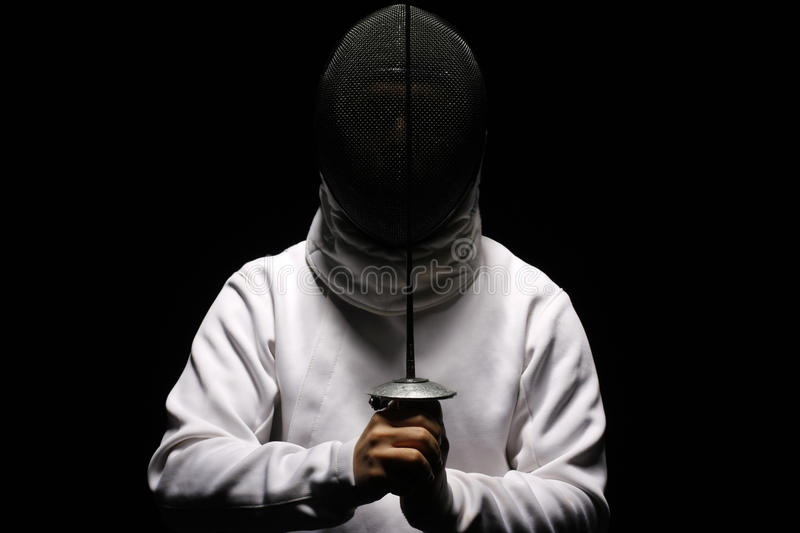 Fencing. Man with sword isolated on black stock images
