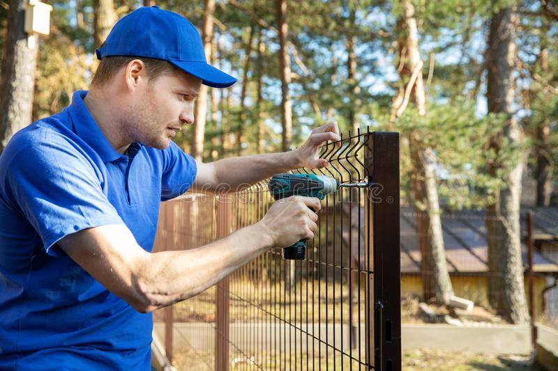 Fencing services - worker installing welded metal mesh fence. Fencing services - worker installing brown welded metal mesh fence panel stock photos
