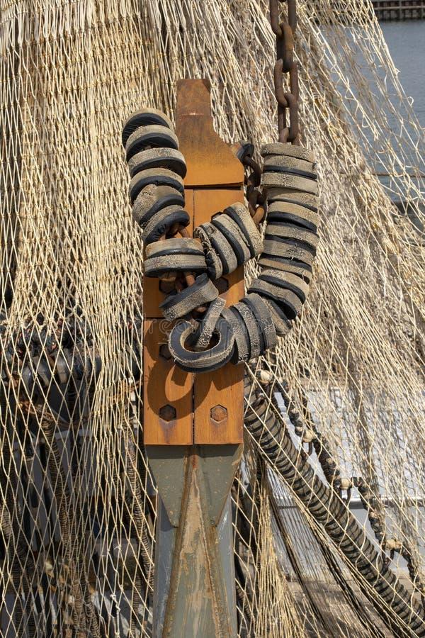Fender na żelazo łańcuchu robić guma przy łodzią rybacką i sieć rybacka, obraz royalty free