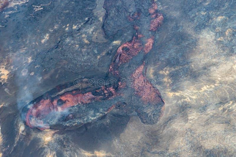 Fenditura attiva nel flusso di lava sulla grande isola delle Hawai Magma rosso visibile; gas vulcanico che aumenta nell'aria fotografia stock