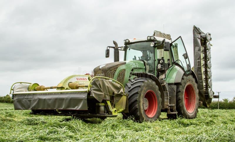 Fendt pone verde el tractor con los cortacéspedes de los claas en campo del ensilaje fotografía de archivo