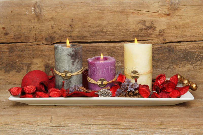 Feng Shui potpourri. Three burning Feng Shui candles in a dish with potpourri against a background of old weathered wood stock photography