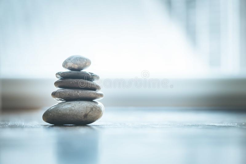 Feng Shui: Zen stones on the wooden floor, bright light is coming through the window. Feng Shui: Stone cairn on the wooden floor, text space and cool light home royalty free stock photos