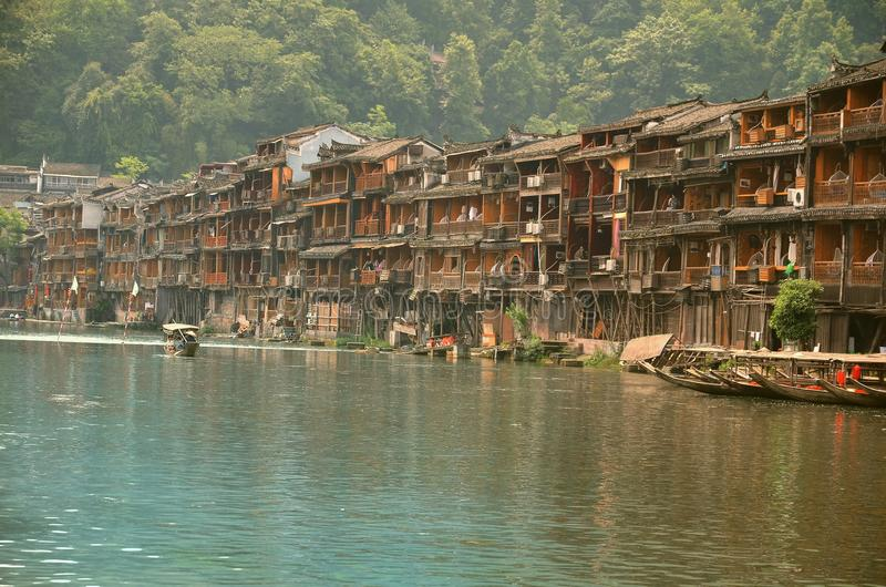 Fenghuang, China - May 14, 2017: People and boats around riverside at the Phoenix Hong Bridge in Fenghuang.  royalty free stock images