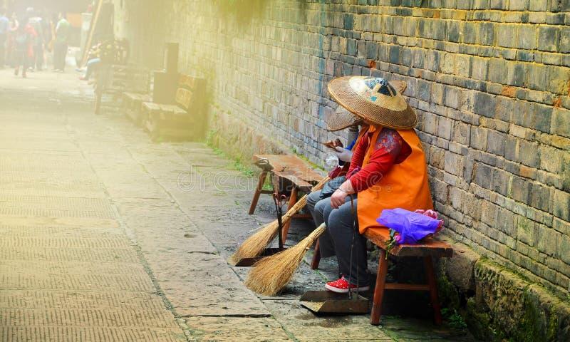 Fenghuang, Chine - 15 mai 2017 : Repos de femme sur la rue dans la ville de Phoenix Fenghuang images stock