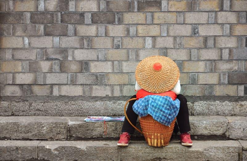 Fenghuang Kina - Maj 15, 2017: Kvinnan vilar på gatan i den Phoenix Fenghuang staden royaltyfria bilder