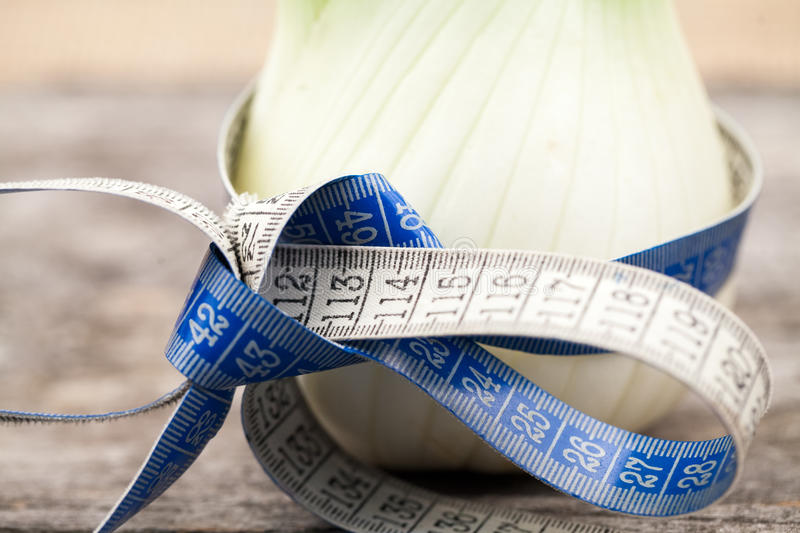 Fennel bulb and tailoring meter on an old wooden surface stock photos