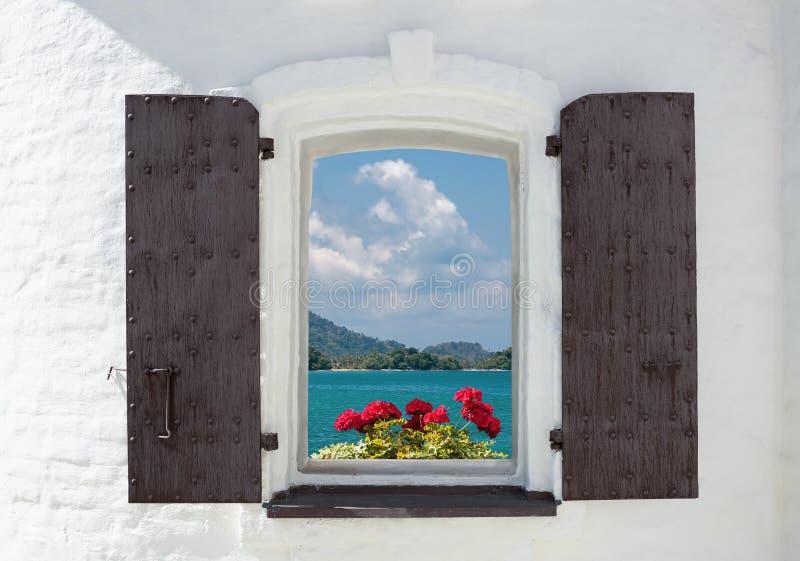 Fenster in einem alten Haus verziert mit Blumen und Seeansicht lizenzfreies stockbild