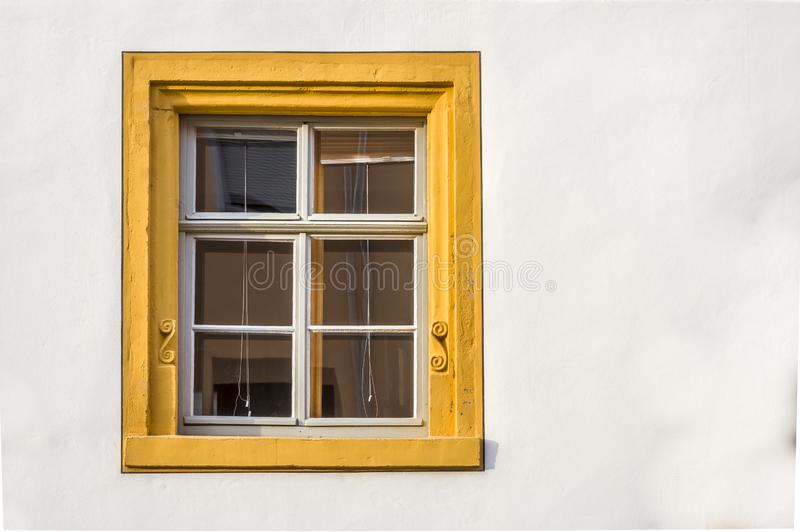 Fenster eines wieder hergestellten Fachwerkhauses teils vergipst mit der Sandsteingestaltung, verziert mit gelber Farbe stockfotografie