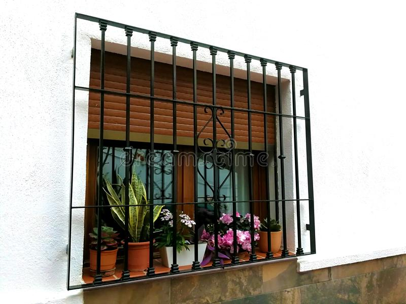 Fenster mit Stangen und Blumentöpfen stockbilder